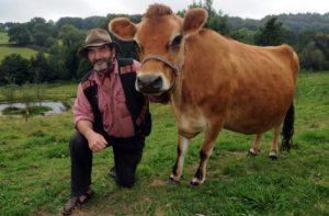 Simon Fairlie, author of 'Meat - a benign extravagance', with a Jersey cow at the Monkton Wyld Court Sustainable Living Commune near Charmouth. Picture: Murray Sanders.